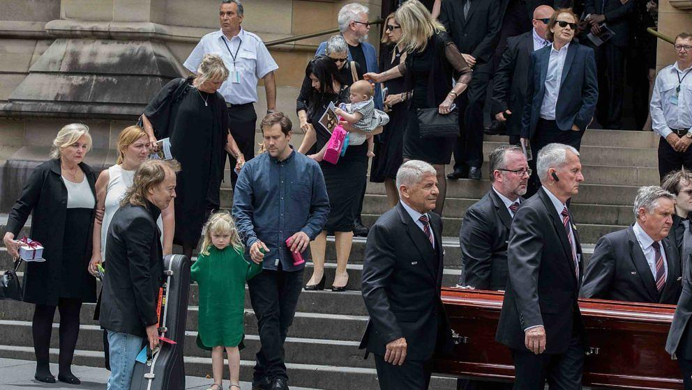 SYDNEY, AUSTRALIA - NOVEMBER 28:  Angus Young follows his brother's coffin out at the funeral service for AC/DC co-founder Ma