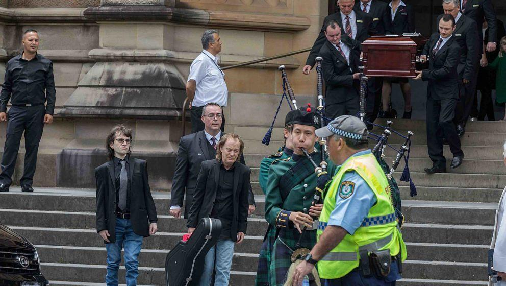 SYDNEY, AUSTRALIA - NOVEMBER 28:  Angus Young with nephew Ross, son of Malcom, follow his brother's coffin out at the funeral