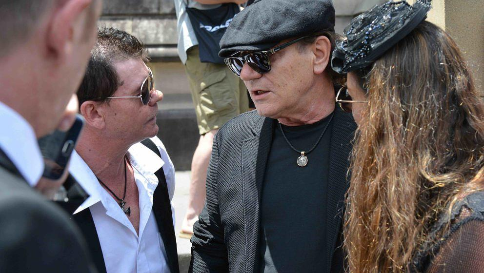 AC/DC lead singer Brian Johnson (C) speaks with attendees after the funeral service of AC/DC co-founder Malcolm Young outside