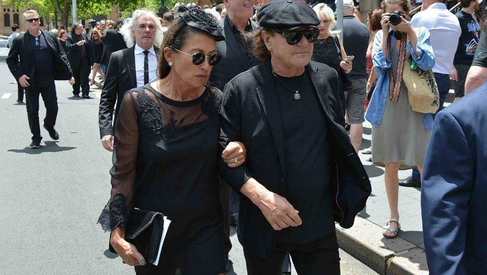 AC/DC lead singer Brian Johnson (R) and his wife Brenda (C) walk in front of AC/DC bassist Cliff Williams (behind L-white hai