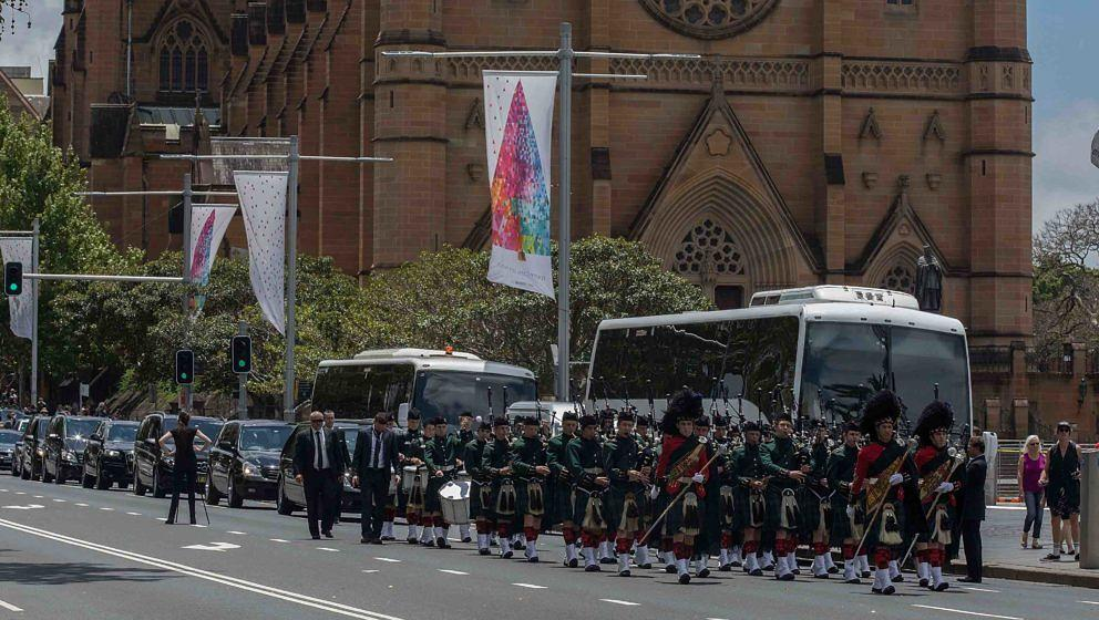 SYDNEY, AUSTRALIA - NOVEMBER 28:  Pipers fron Svott's College accompany the funeral cortege down College Street after  the fu