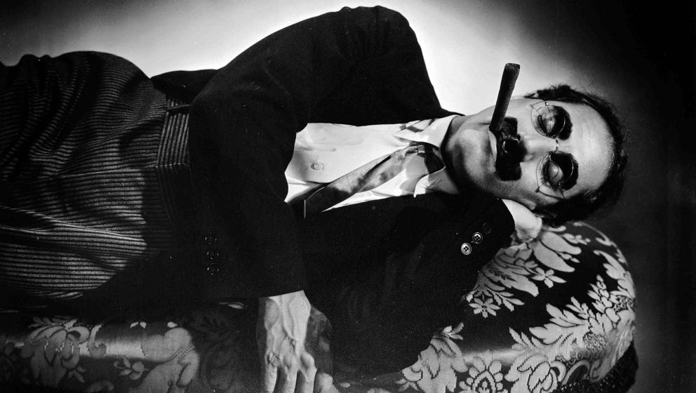circa 1935:  American actor Groucho Marx (1895 - 1977) sleeps on a couch with a cigar still clamped between his lips.  (Photo