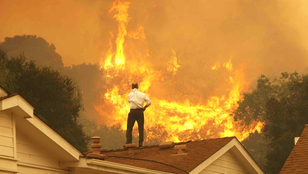 CAMARILLO, CA - MAY 3:  A man on a rooftop looks at approaching flames as the Springs fire continues to grow on May 3, 2013 n