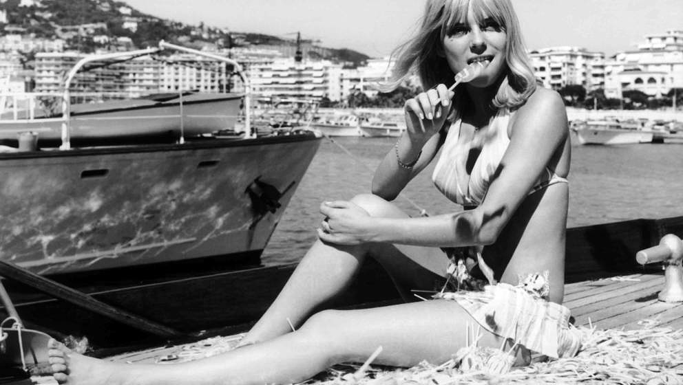 FRANCE - MAY 11:  France GALL in a two-piece swimsuit, sitting among a pile of lollipops with one in her mouth, on the French