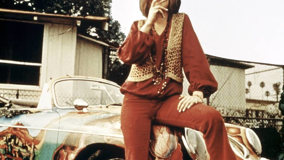 American singer-songwriter Janis Joplin (1943 - 1970) with her 1965 Porsche 356C Cabriolet, circa 1969. The car features a ps