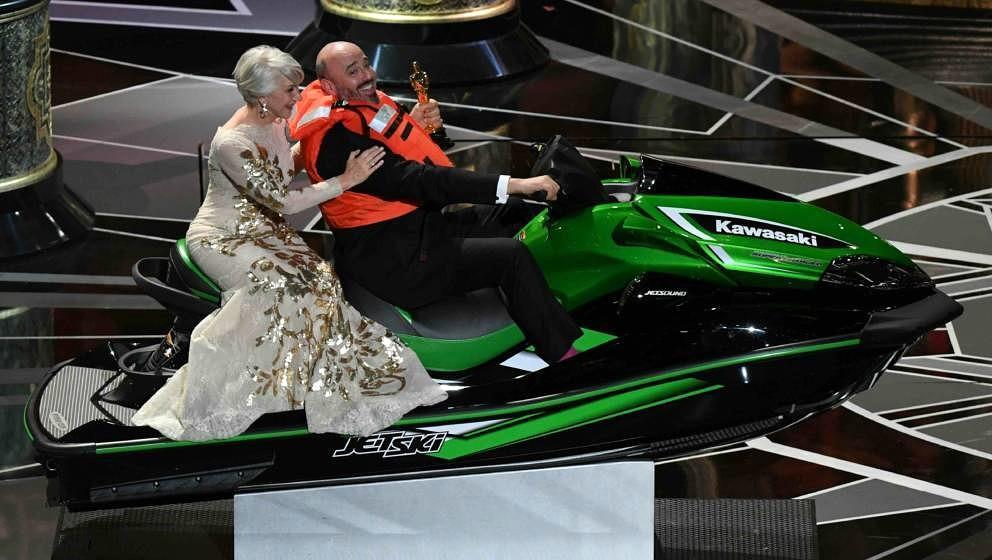British actress Helen Mirren (L) rides with jet ski winner and laureate for Costume Design Mark Bridges after the Oscar cerem