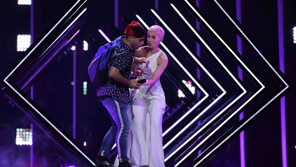 A man takes the microphone from Britain's singer Susanna Marie Cork aka SuRie as she performs 'Storm' during the final of the