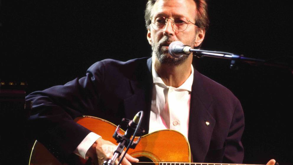 Eric Clapton performs on stage playing acoustic guitar at the Royal Albert Hall, London, 1998. (Photo by Phil Dent/Redferns)