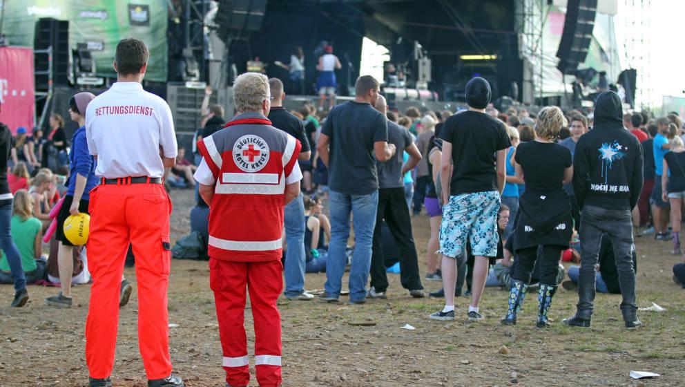 Ein Sanitäter und ein Notarzt stehen hinter Festival-Besuchern