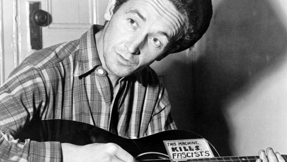 Folk singer Woody Guthrie poses for a portrait with his guitar which has a sign on it that reads 'This Machine Kills Fascists