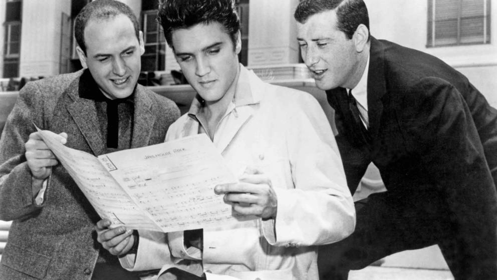 CULVER CITY, CA - 1957:  Rock and roll singer Elvis Presley with songwriters Leiber and Stoller looking over the sheet music