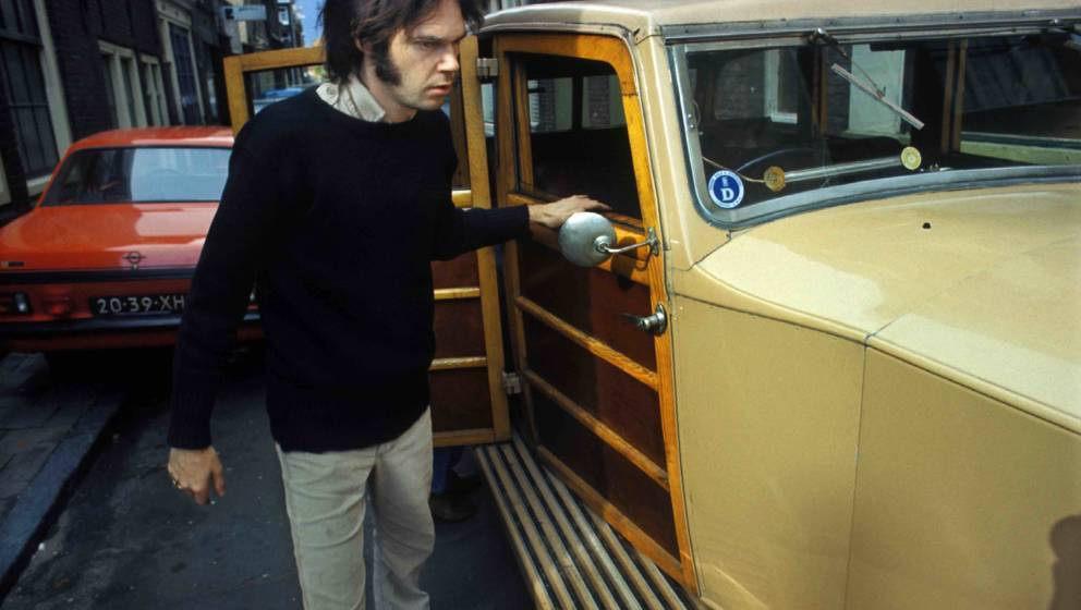 AMSTERDAM, NETHERLANDS: Neil Young checks over The Rolls Royce car he has just purchased in Jordaan, Amsterdam, Netherlands i