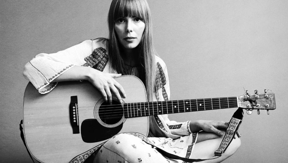 20th November 1968:  Portrait of American musician Joni Mitchell seated on the floor with her acoustic guitar in her lap.  Th