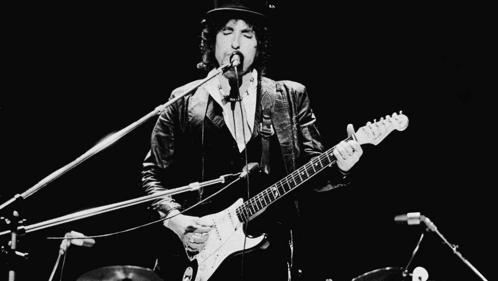 American singer and songwriter Bob Dylan sings and plays guitar on stage, wearing a top hat, during the Blackbushe Pop Festiv