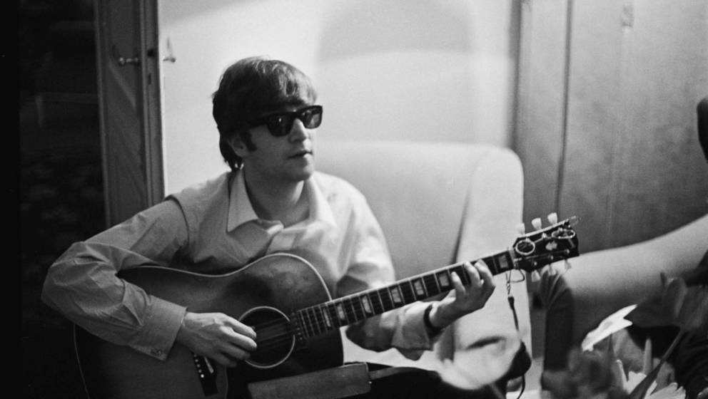 John Lennon (1940 - 1980) of the Beatles plays the guitar in a hotel room in Paris, 16th January 1964. (Photo by Harry Benson