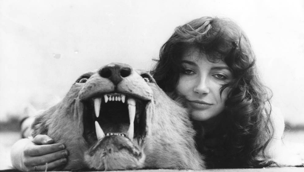 English singer-songwriter and musician Kate Bush posing on a lion skin rug at her family's home in East Wickham, London, 26th