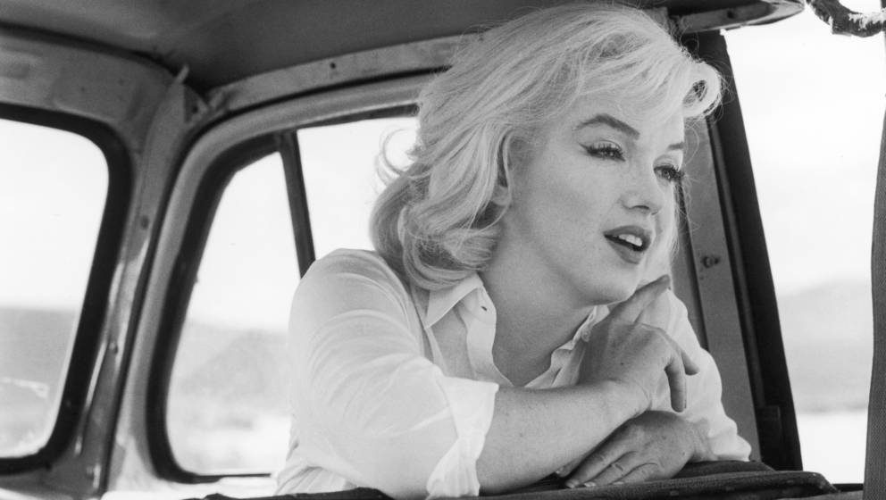 American actress Marilyn Monroe (1926 - 1962) (born Norma Jean Mortensen) leans over the back of the front seat of a car on t