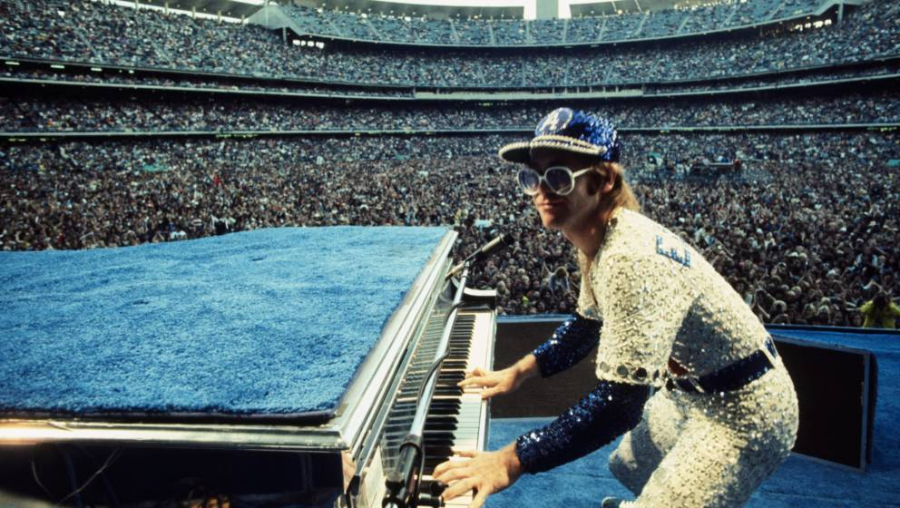 English singer songwriter Elton John performing at Dodger Stadium in Los Angeles, 1975. He is wearing a sequinned baseball ou