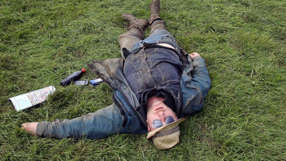 GLASTONBURY, ENGLAND - JUNE 23:  A man sleeps in front at the Pyramid Stage at the Glastonbury Festival site at Worthy Farm,