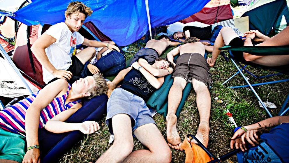 A groups of festival guest are taking a rest and enjoy some relaxation in the festival camp before another party night goes o