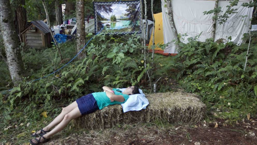 HAPPY VALLEY, OREGON, AUGUST 01: A camper takes a nap on a bale of hay at the Pickathon music festival on August 1, 2014 in H