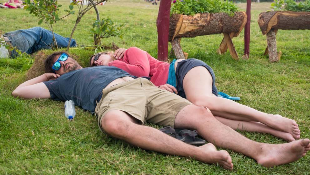GLASTONBURY, ENGLAND - JUNE 27: Festival goers sleep on the grass at the Glastonbury Festival at Worthy Farm, Pilton on June