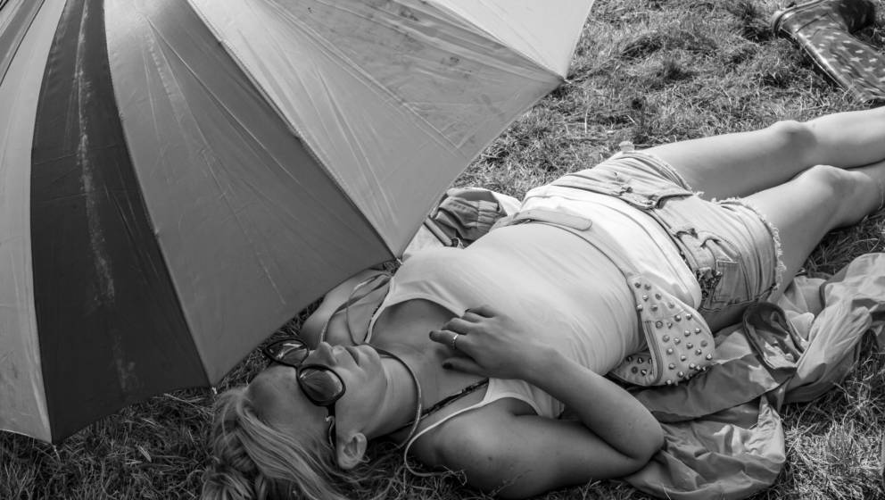 GLASTONBURY, ENGLAND - JUNE 27: (EDITORS NOTE: This images has been converted to Black and White) A festival goer sleeps unde