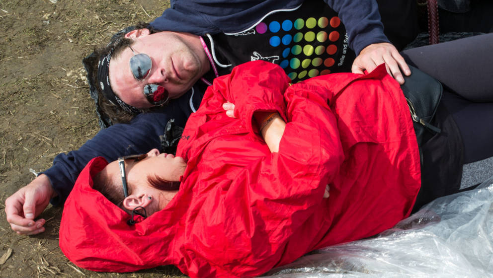 GLASTONBURY, ENGLAND - JUNE 28: Festival goers sleep on the ground at the Glastonbury Festival at Worthy Farm, Pilton on June