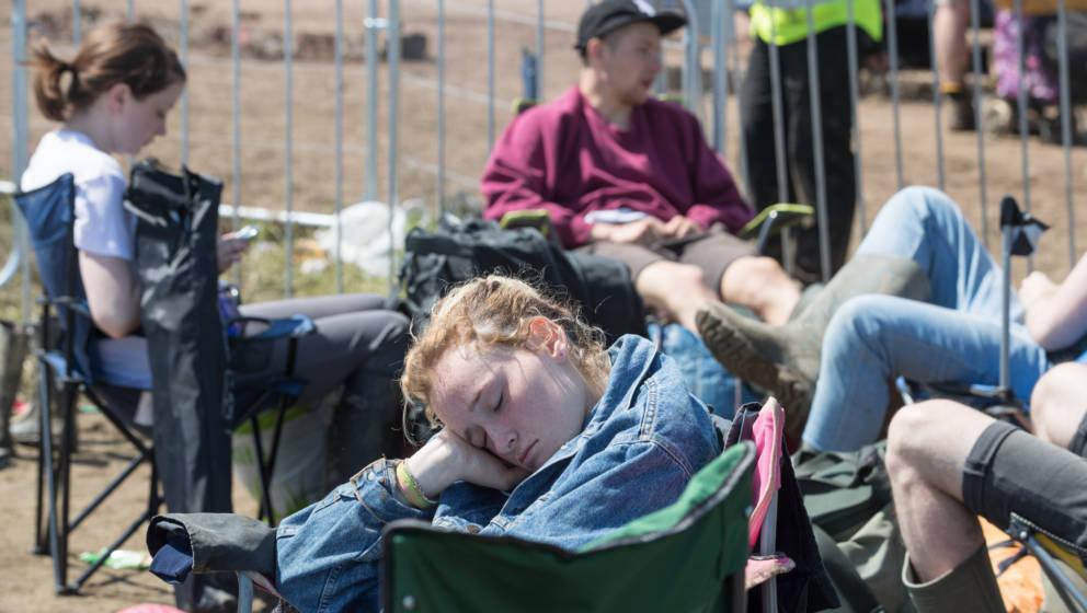 GLASTONBURY, ENGLAND - JUNE 27:  A girl sleeps as she waits for a bus as festival goers leave the Glastonbury Festival 2016 a