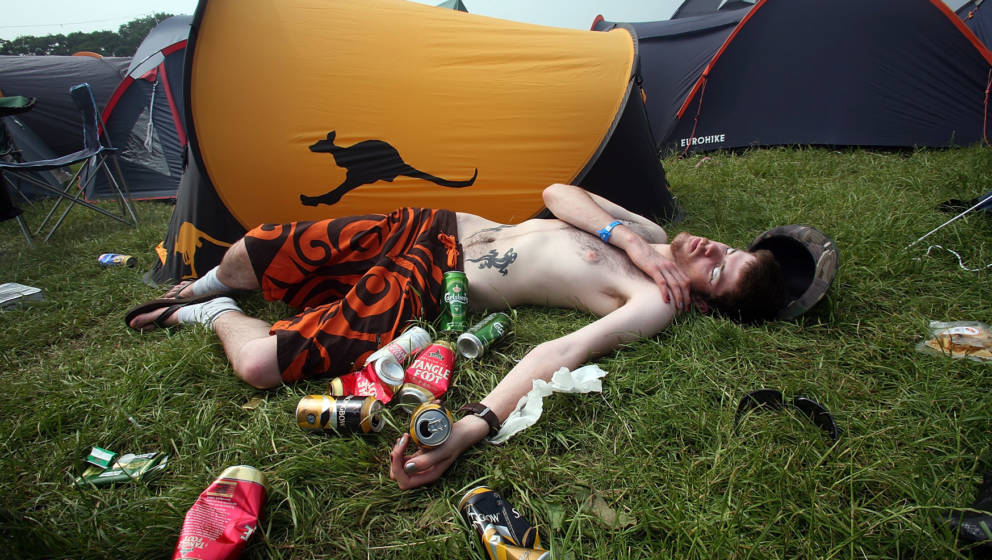 NEWPORT, UNITED KINGDOM - JUNE 08:  A festival reveller sleeps on the grass outside his tent in the campsite on the first day