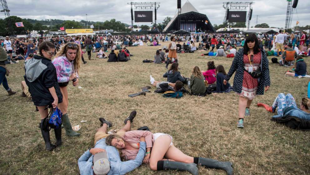 GLASTONBURY, ENGLAND - JUNE 25:  A woman sleeps on her partner's chest during the afternoon at the Pyramid Stage at Glastonbu