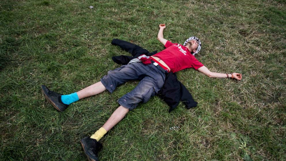 GLASTONBURY, ENGLAND - JUNE 25:  A man sleeps on the ground during the afternoon at the Pyramid Stage at Glastonbury Festival