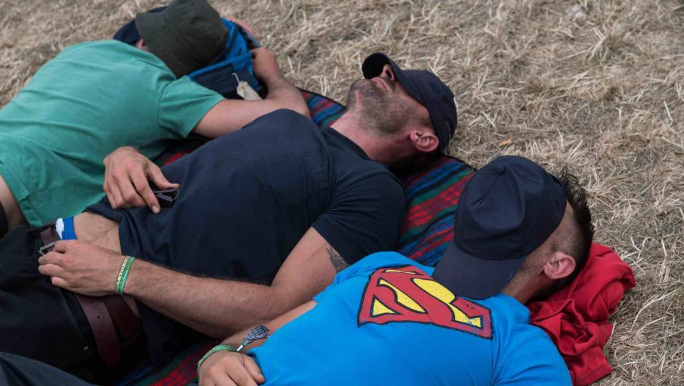 GLASTONBURY, ENGLAND - JUNE 25:  Three men, one wearing a Superman t-shirt, sleep during the afternoon at the Pyramid Stage a