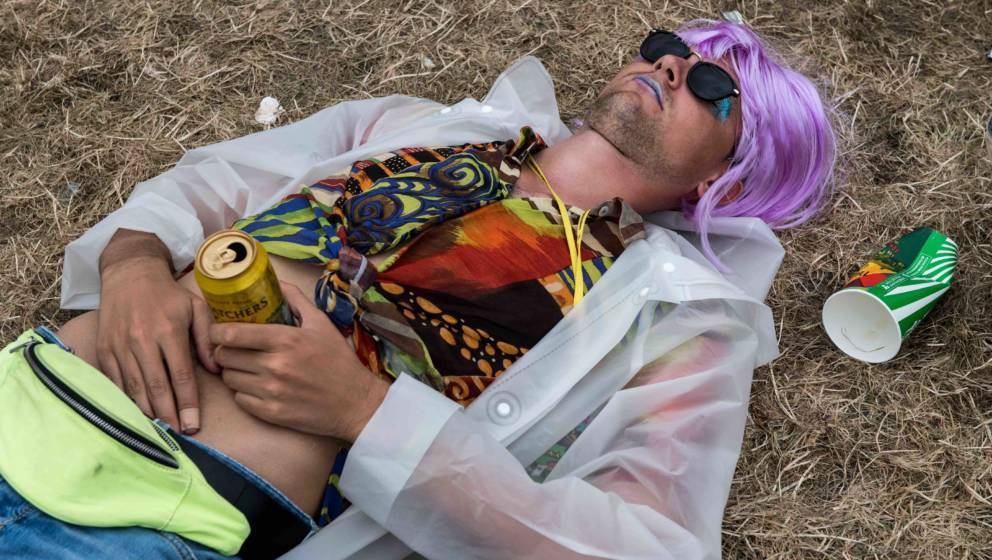 GLASTONBURY, ENGLAND - JUNE 25:  A man clutches a can of cider whilst sleeping during the afternoon at the Pyramid Stage at G