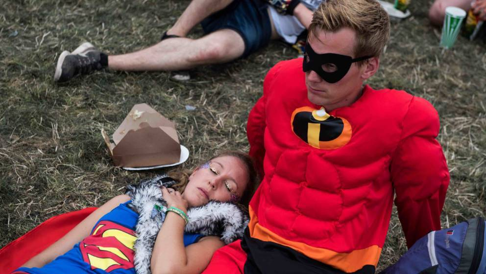 GLASTONBURY, ENGLAND - JUNE 25:  A woman dressed as Superwoman sleeps next to her partner dressed as Mr Incredible during the