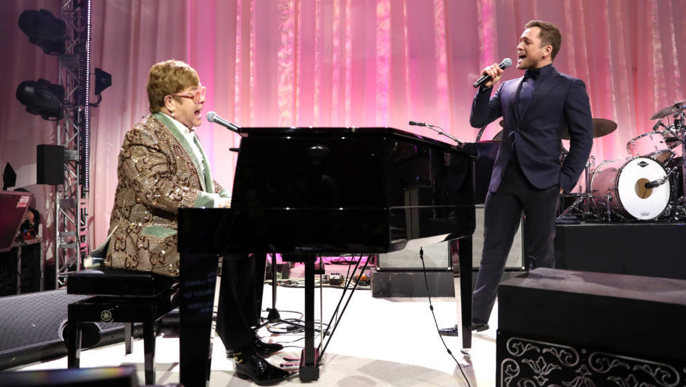 WEST HOLLYWOOD, CA - FEBRUARY 24:  Sir Elton John and Taron Egerton perform onstage during the 27th annual Elton John AIDS Fo