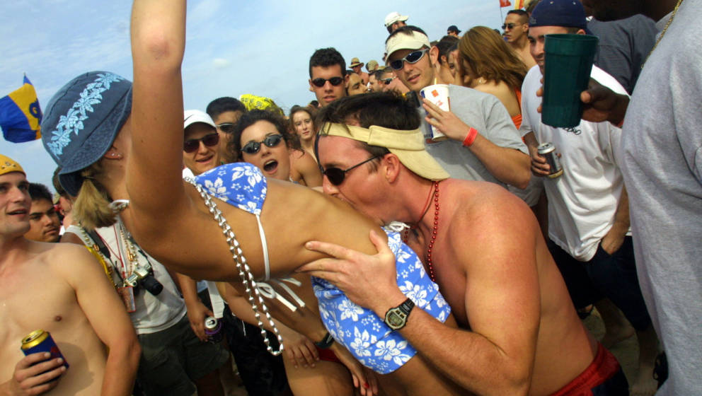 386746 04: A man kisses a woman's stomach on the beach at South Padre Island, Texas March 16, 2001 during the annual rite of