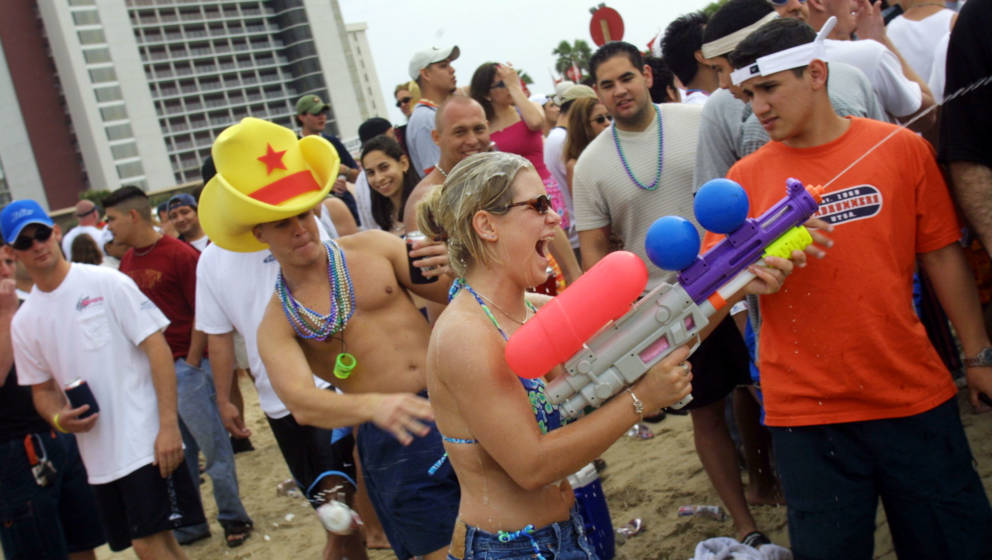 386746 15: A student shoots a water gun on the beach at South Padre Island, Texas March 16, 2001 during the annual rite of Sp
