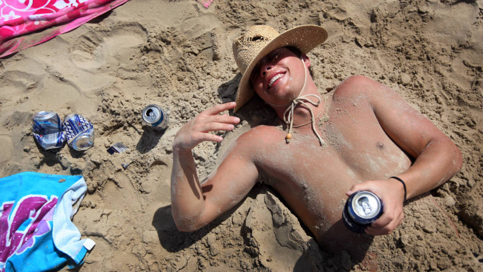 SOUTH PADRE ISLAND, TX - MARCH 25:  A drunken student lies half buried in sand on the beach during the annual ritual of Sprin