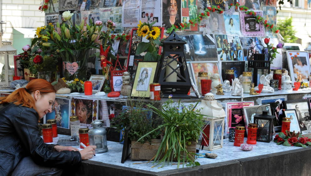 A woman kneels beside flowers, letters and pictures of the King of Pop Michael Jackson which are fixed on a monument dedicate