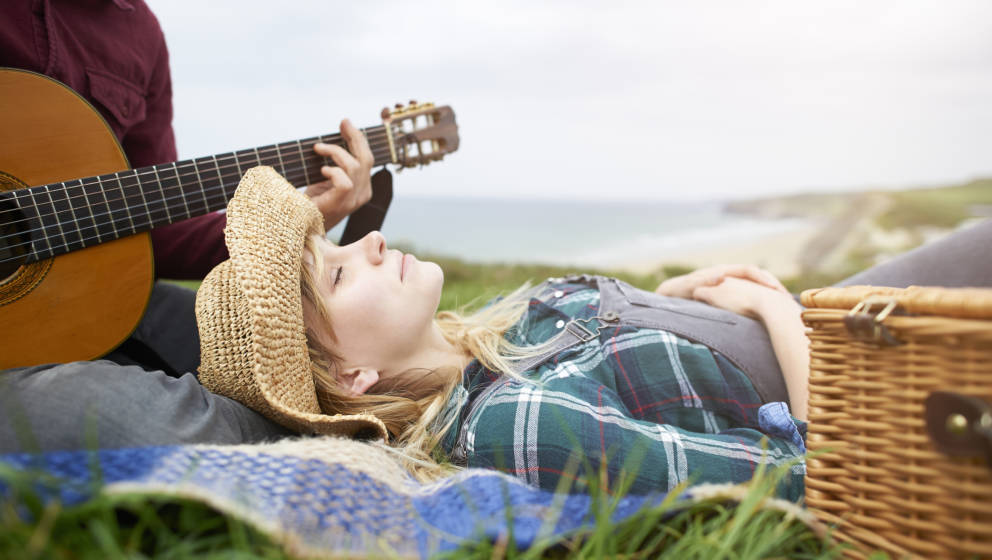 A woman lays with eyes closed on an Atlantic coastline with a picnic basket and blanket whilst her partner plays the guitar.