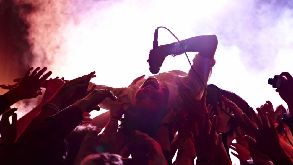 Rock concert with many excited people cheering and waving. The lead singer is crowd surfing.