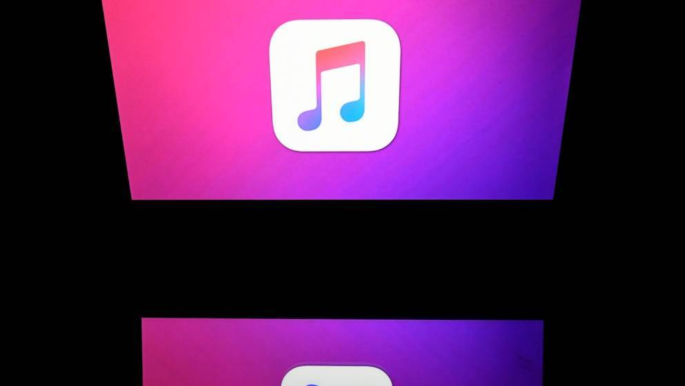 This illustration picture taken on April 19, 2018 shows the logo of the Itunes app of Apple displayed on a tablet screen in P
