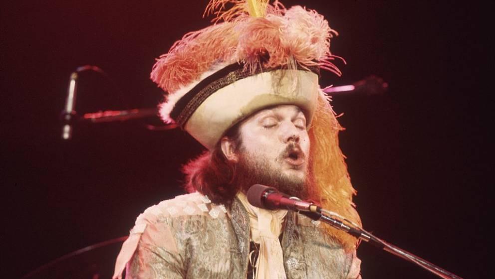 circa 1975:  New Orleans R&B and rock pianist Mac Rebennack, a.k.a. Dr. John, sings at a microphone, wearing a headdress
