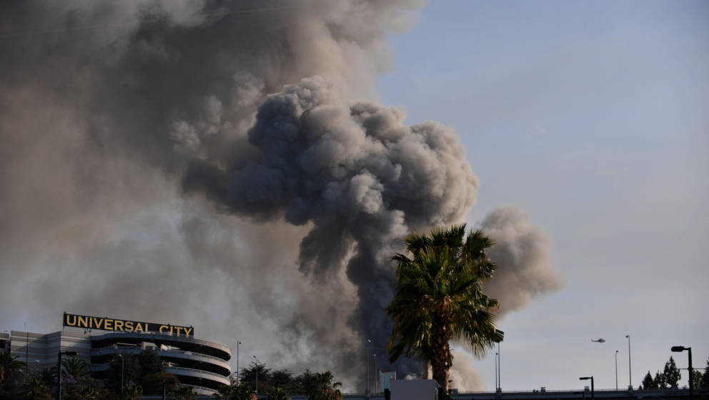 Smoke rises over burning structures at Universal Studios, in Universal City, California, on June 01, 2008. More than 100 fire