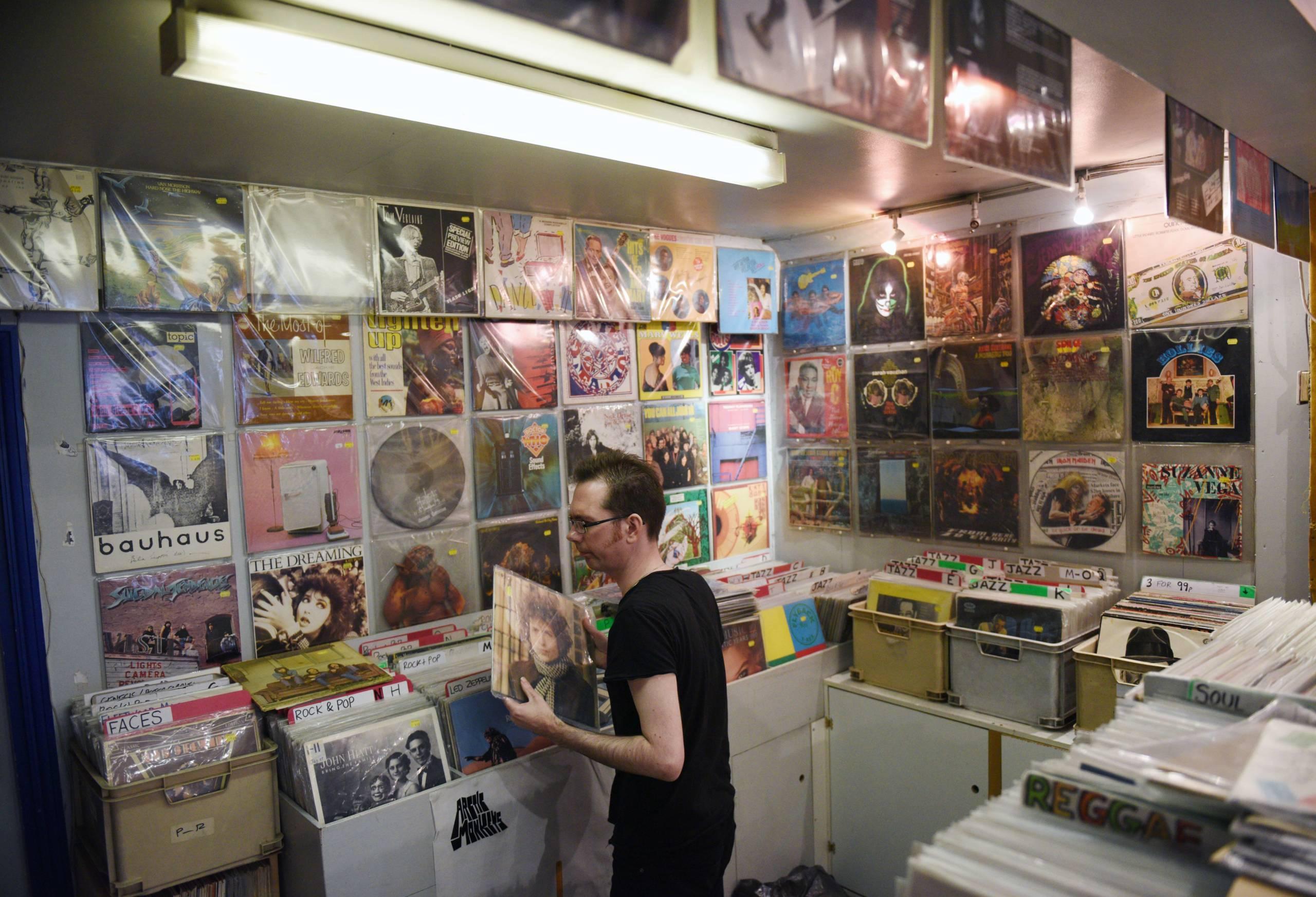 """Ein Mitarbeiter von """"Record Collector"""" Shop sortiert Platten"""