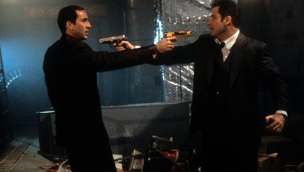 Nicolas Cage and John Travolta aiming guns at each other in a scene from the film 'Face/Off', 1997. (Photo by Touchstone/Gett