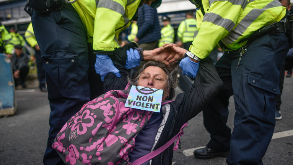 LONDON, ENGLAND - OCTOBER 10: A protester is removed by police as climate change action group Extinction Rebellion stage a pr