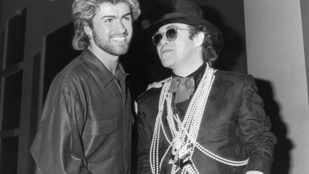 Pop star Elton John (right) congratulates George Michael on winning the Ivor Novello Songwriter of the Year Award at London's