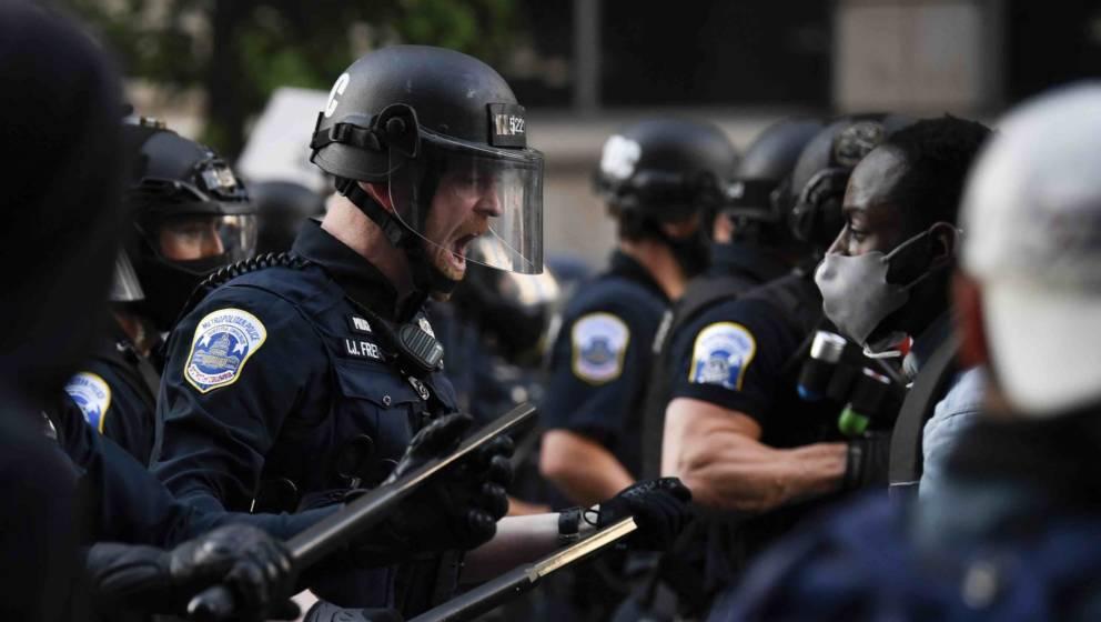 Ein Polizist in Kampfausrüstung reagiert mit deutlichen Worten auf Demonstranten, die sich in der Nähe des Weißen Hauses i
